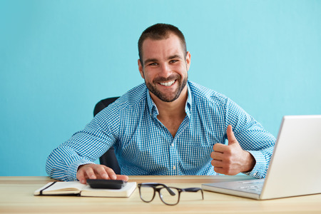 Smiling businessman calculates taxes and gestures with a thumbs up to portray the concept of tax credits.